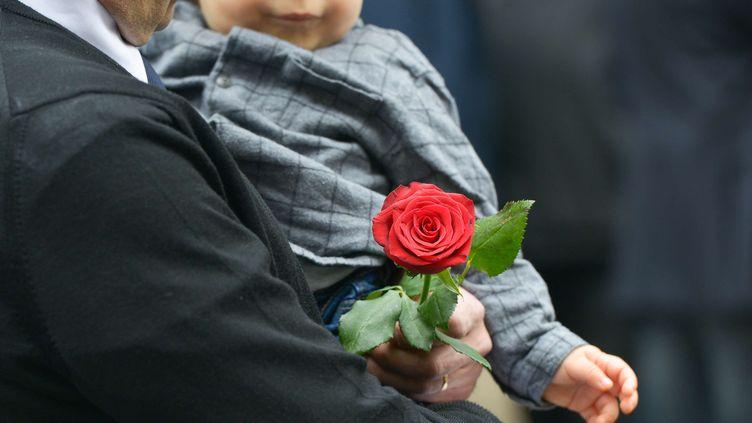 Un homme tient une rose à la main, devant le siège du PS, le 14 mai 2017. (ISA HARSIN / SIPA)