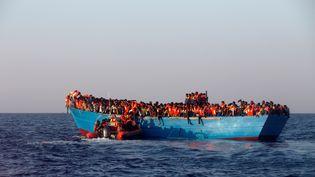 Un bateau de l'ONG espagnole Proactiva approche une embarcation transportant des migrants en mer Méditerranée, au large de la Libye, le 29 août 2016. (GIORGOS MOUTAFIS / REUTERS)