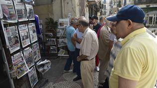 AAlger, le 16 septembre 2019, des passants regardent les unes des journaux nationaux et étrangers annonçant la date de l'élection présidentielle. (RYAD KRAMDI / AFP)