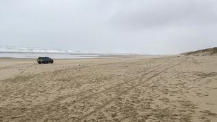 Une voiture de police sur la plage du Gressier au Porge (Gironde) où des ballots de cocaïne ont été découverts. (CAMILLE CASSOU / AFP)