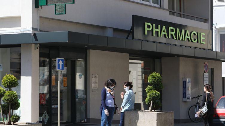 Des femmes avec un masque devant une pharmacie à Mulhouse dans le Haut-Rhin, le 27 avril. (VINCENT VOEGTLIN / MAXPPP)