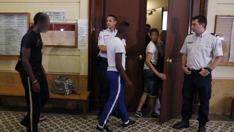 Trois hommes suspectés d'avoir pris part aux violences à Trappes entrent dans la salle d'audience du tribunal de Versailles (Yvelines), le 22 juillet 2013. (FRANCOIS GUILLOT / AFP)