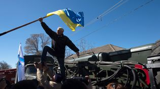 Un pro-russe retire un drapeau ukrainien dans la base aérienne deNovofedorivka, le 22 mars 2014, en Crimée. (DMITRY SEREBRYAKOV / AFP)