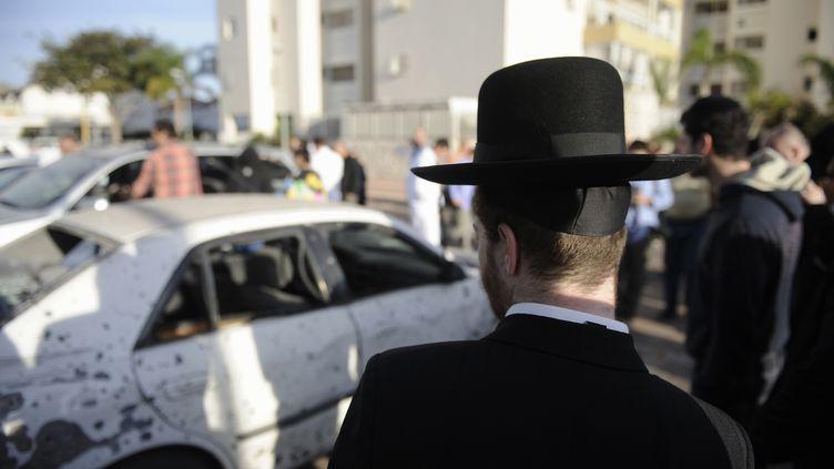 Un juif ultra-orthodoxe regarde une voiture détruite par une roquette palestinienne, le16 novembre 2012 à Ashdod (Israël). (DAVID BUIMOVITCH / AFP)