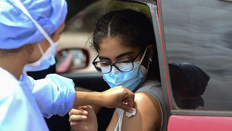 Une adolescente hondurienne reçoit une dose de vaccin contre le Covid-19, samedi 25 septembre 2021 à Tegucigalpa. (ORLANDO SIERRA / AFP)