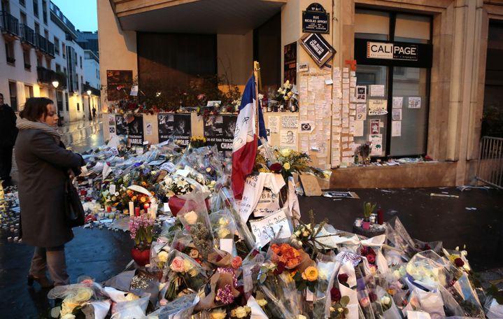 """Une femme contemple les fleurs et mots déposés à l'entrée de la rue Nicolas-Appert, en hommage aux onze victimes de l'attentat du 7 janvier 2015 dans les locaux de""""Charlie Hebdo"""". ((JACQUES DEMARTHON / AFP))"""