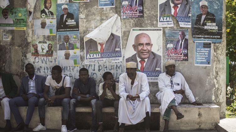 Des Comoriens devant un mur d'affiches, lors de la campagne présidentielle en mars 2019. (GIANLUIGI GUERCIA / AFP)