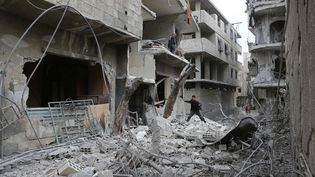 Un jeune Syrien examine le site bombardé d'Hamouria, dans la région de la Ghouta orientale (Syrie), le 22 février 2018. (ABDULMONAM EASSA / AFP)