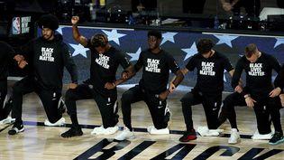 Des joueurs de NBA s'agenouillent pour rendre hommage au mouvement Black lives matter à Lake Buena Vista, en Floride, le 13 août 2020. (GETTY IMAGES NORTH AMERICA / AFP)