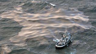"""Un remorqueur tente d'aspirer une nappe de fioul échappée de l'""""Erika"""", le 15 décembre 2012, au large de la Bretagne. (VALERY HACHE / AFP)"""