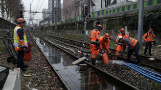Des employés de la SNCF pompent l'eau sur les voies du RER C, à la station Javel, dimanche 28 janvier 2018. (THOMAS SAMSON / AFP)