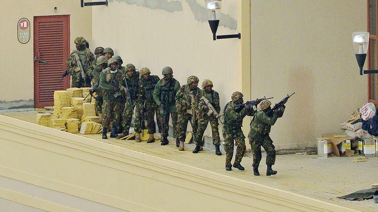 Des soldats kényans avancent en formation, le 24 septembre 2013, lors de l'assaut final contre les islamistes présents dans le centre commercial Westgate à Nairobi (Kenya). (CARL DE SOUZA / AFP)