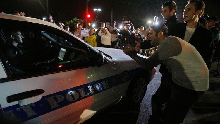 Des habitants de Boston félicitent les policiers après l'arrestation de Djokhar Tsarnaev, le second suspect de l'attentat de la ville, le 19 avril 2013. (BRIAN SNYDER / REUTERS)