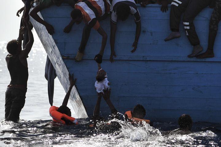 Des migrants tentent de protégerun enfant suspendu au-dessus de l'eau au large des côtes libyennes, le 4 octobre 2016. (ARIS MESSINIS / AFP)