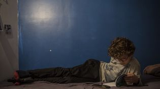Un garçon lit un roman allongé sur son lit (2020) (CELINE GAILLE / HANS LUCAS)