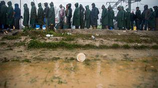 La vie quotidienne des migrants est rythmée par la queue qu'il doivent faire pour obtenir de la nourriture, du bois ou encore un thé après la forte pluie qui s'est abattue sur le campe d'Idomeni le 9 mars 2016. (ZOLTAN BALOGH / MTI)