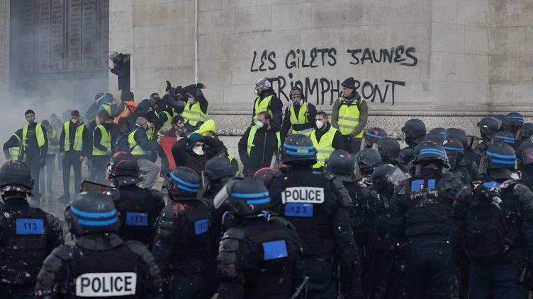 """Des """"gilets jaunes"""" manifestent sous l'Arc de Triomphe, le 1er décembre 2018. (GEOFFROY VAN DER HASSELT / AFP)"""