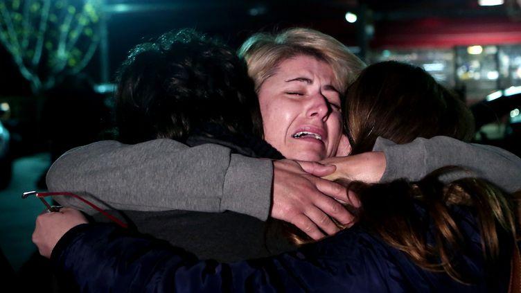 """Une rescapée du ferry """"Norman Atlantic"""" enlace ses enfants après avoir été rapatriée à Athènes (Grèce), le 29 décembre 2014. (ANGELOS TZORTZINIS / AFP)"""