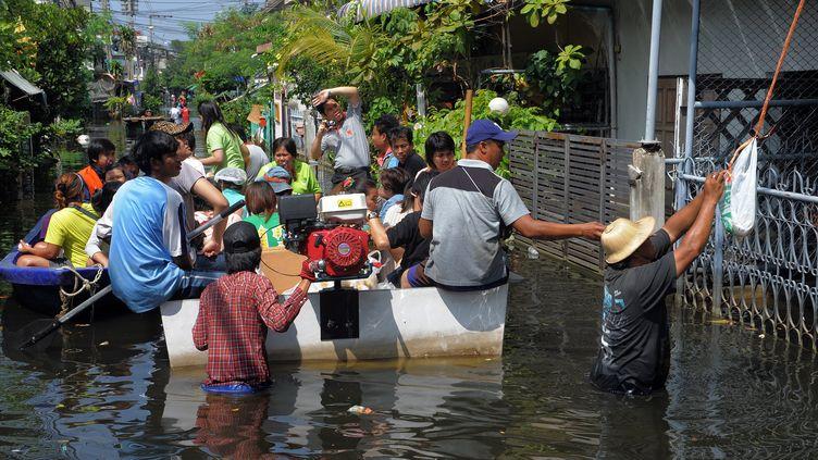 Des habitants de Bangkok se déplacent en barques dans les rues inondées de la capitale thaïlandaise, le 2 novembre 2011. (TANG CHHIN SOTHY / AFP)