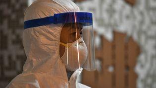 Un membre du personnel médical dans une résidence où deux personnes ont été testées positives au coronavirus, à Hong Kong, le 11 février 2020. (ANTHONY WALLACE / AFP)