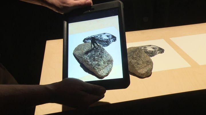 On déplace la tablette au-dessus des pierres et, miracle (ou mirage ?), un petit génie apparaît sur l'une d'entre elles...Mirages & Miracles, une série d'installations proposées auxChamps Libres à Rennes. (V. Bars / France Télévisions)