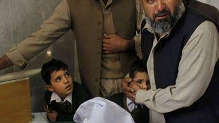 Un Pakistanaise réconforte un élève debout au chevet d'un jeune garçon blessé dans l'attaque des talibans sur une école dePeshawar (Pakistan)le 16 décembre 2014. (MOHAMMAD SAJJAD / AP/ SIPA )