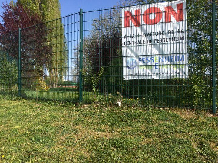 De nombreuses affiches condamnent le projet de fermeture de la centrale nucléaire, à Fessenheim (Haut-Rhin), le 6 avril 2017. (LICIA MEYSENQ / FRANCEINFO)