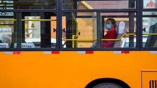 Une passagère d'un bus àManzhouli, au nord de la Chine, le 14 avril 2020. (LIAN ZHEN / XINHUA / AFP)