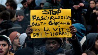 """Lors d'une manifestation contre le racisme à Macerata (Italie) samedi 10 février, un manifestant brandit une pancarte """"Stop au fascisme et au racisme, arrêtez de jouer avec la vie des migrants"""". (TIZIANA FABI / AFP)"""
