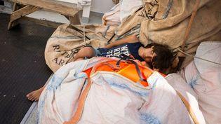 Un jeune homme dort sur le pont de l'Aquarius, balancé par la houle. (MAUD VEITH / SOS MEDITERRANEE)