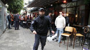 Un policier israélien court après la fusillade qui a éclaté dans un bar du centre de Tel-Aviv (Israël), le 1er janvier 2016. (NIR ELIAS / REUTERS)