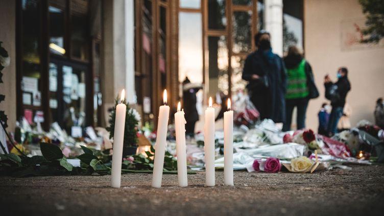 Des bougies déposées en hommage à Samuel Paty devant le collège du Bois d'Aulne, àConflans-Sainte-Honorine (Yvelines), le 17 octobre 2020. (SAMUEL BOIVIN / NURPHOTO / AFP)