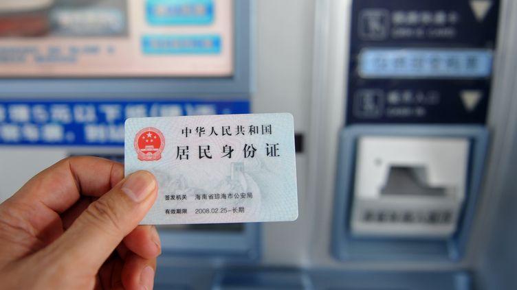 Un passager utilise sa carte d'identité pour acheter un billet de train à Qionghai (Chine), le 26 août 2013. (MENG ZHONGDE / IMAGINECHINA / AFP)