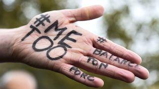 Les messages #metoo et #balancetonporc sur la main d'une manifestante lors d'un rassemblement contre le harcèlement et les agressions sexuels, place de la République à Paris le 29 octobre 2017. (BERTRAND GUAY / AFP)