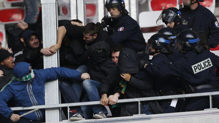 Des supporters affrontent les forces de l'ordre dans les tribunes dans le stade de l'Allianz Riviera à Nice, le dimanche 24 novembre 2013, avant le début du matchOGC Nice-AS Saint-Etienne. (VALERY HACHE / AFP)