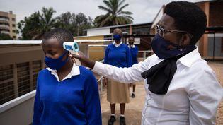 Des élèves du lycée Notre-Dame de Citeaux à Kigali (Rwanda) se font prendre la température avant d'entrer en classe, le 2 novembre 2020. (SIMON WOHLFAHRT / AFP)