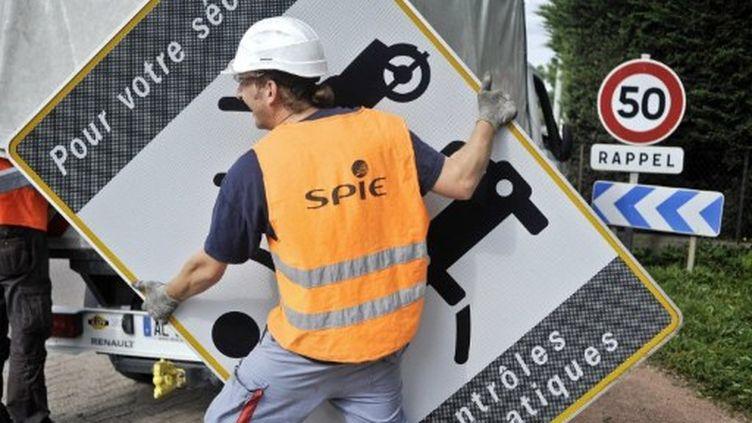 démontage de panneau avertissant de la présence d'un radar, le 16 mai 2011 à Dijon (AFP PHOTO / JEFF PACHOUD)