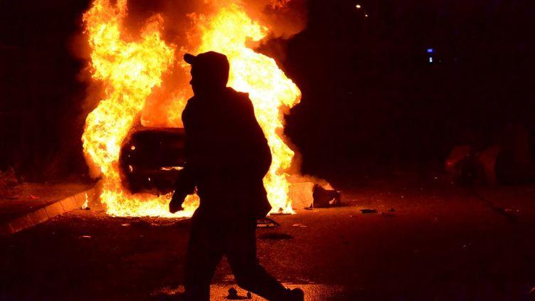 Un manifestant anti-confinement passe devant une voiture en train de brûler, lors d'affrontements avec les forces de l'ordre dans le port de Tripoli, au Liban, le 26 janvier 2021. (FATHI AL-MASRI / AFP)
