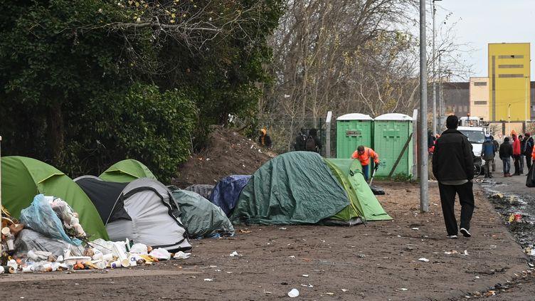 Des migrants marchent dans un camp à Calais (Pas-de-Calais), le 26 novembre 2019. (DENIS CHARLET / AFP)