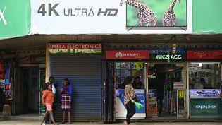 Une femme passe devant un magasin de téléphonie mobile dans l'Avenue Luthuli, au cœur de la ville de Nairobi, la capitale kényane, le 22 mai 2019. (SIMON MAINA / AFP)