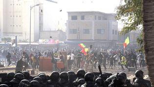Des manifestants face aux gendarmes, dans le quartier deColobane, à Dakar (Sénégal), le 5 mars 2021. (SEYLLOU / AFP)