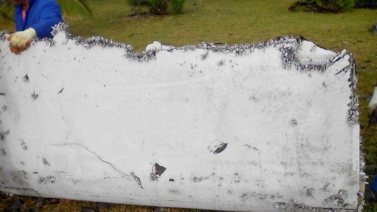 Un fragment d'aile retrouvé sur l'île française de La Réunion, dans l'océan Indien, et appartenant, selon les autorités malaisiennes et la justice française, au Boeing 777 de Malaysia Arlines, le 6 août 2015. (ROMAIN LATOURNERIE / NURPHOTO / AFP)