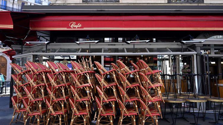 Des piles de chaises devant un restaurant fermé à Paris, le 31 mars 2021. (BERTRAND GUAY / AFP)