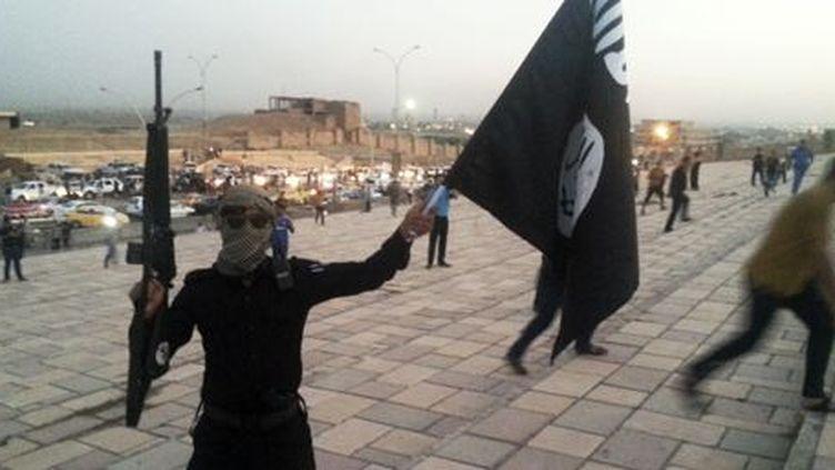 Combattant de Daech avec le drapeau de l'organisation djihadiste à Mossoul (Irak), le 24 juin 2014. (Reuters - Stringer)