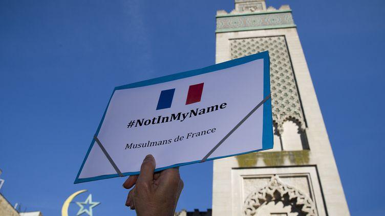 """Un homme brandit une pancarte """"#NotInMyName"""" pendant un rassemblement en hommage à Hervé Gourdel, devant la Grande mosquée de Paris, le 26 septembre 2014. (JOEL SAGET / AFP)"""