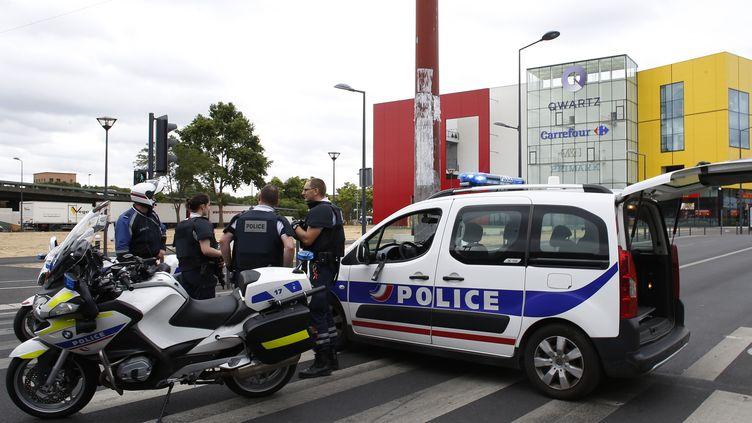 Des policiers devant un centre commercial de Villeneuve-la-Garenne (Hauts-de-Seine), le 13 juillet 2015. (THOMAS SAMSON / AFP)