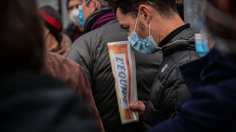 Un employé tient dans sa main un exemplaire du journal l'Equipe pendant une manifestation de la rédaction devant le siège social du groupe.  (MARTIN BUREAU / AFP)