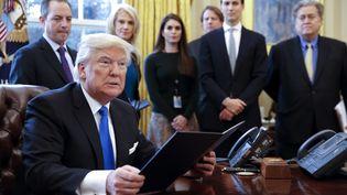 Le président américain Donald Trump, le 24 janvier 2017 dans le bureau ovale de la Maison Blanche, à Washington (Etats-Unis), avec des membres de son équipe. (SHAWN THEW / CNP / AFP)
