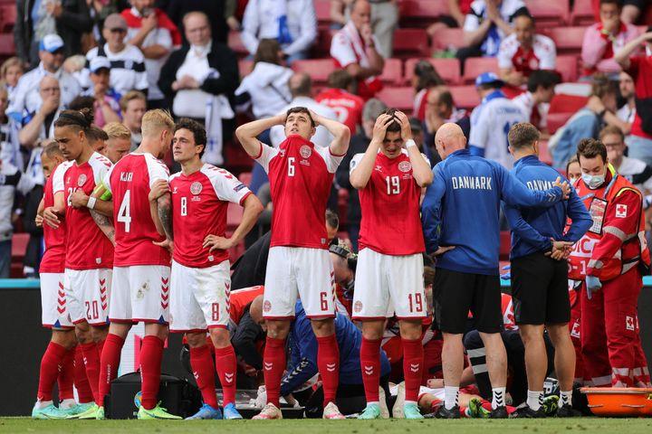 Les Danois réunis autour de Christian Eriksen après sonarrêt cardiaque sur le terrain, lors de Danemark - Finlande à l'Euro, samedi 12 juin 2021. (FRIEDEMANN VOGEL / POOL)