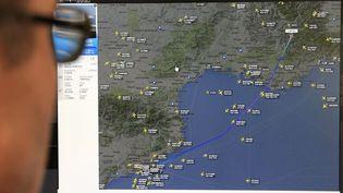 Un homme regarde sur un écran la trajectoire empruntée par l'Airbus A320 qui s'est écrasé dans les Alpes-de-Haute-Provence, le 24 mars 2015, avec 150 personnes à bord. (MAXPPP)